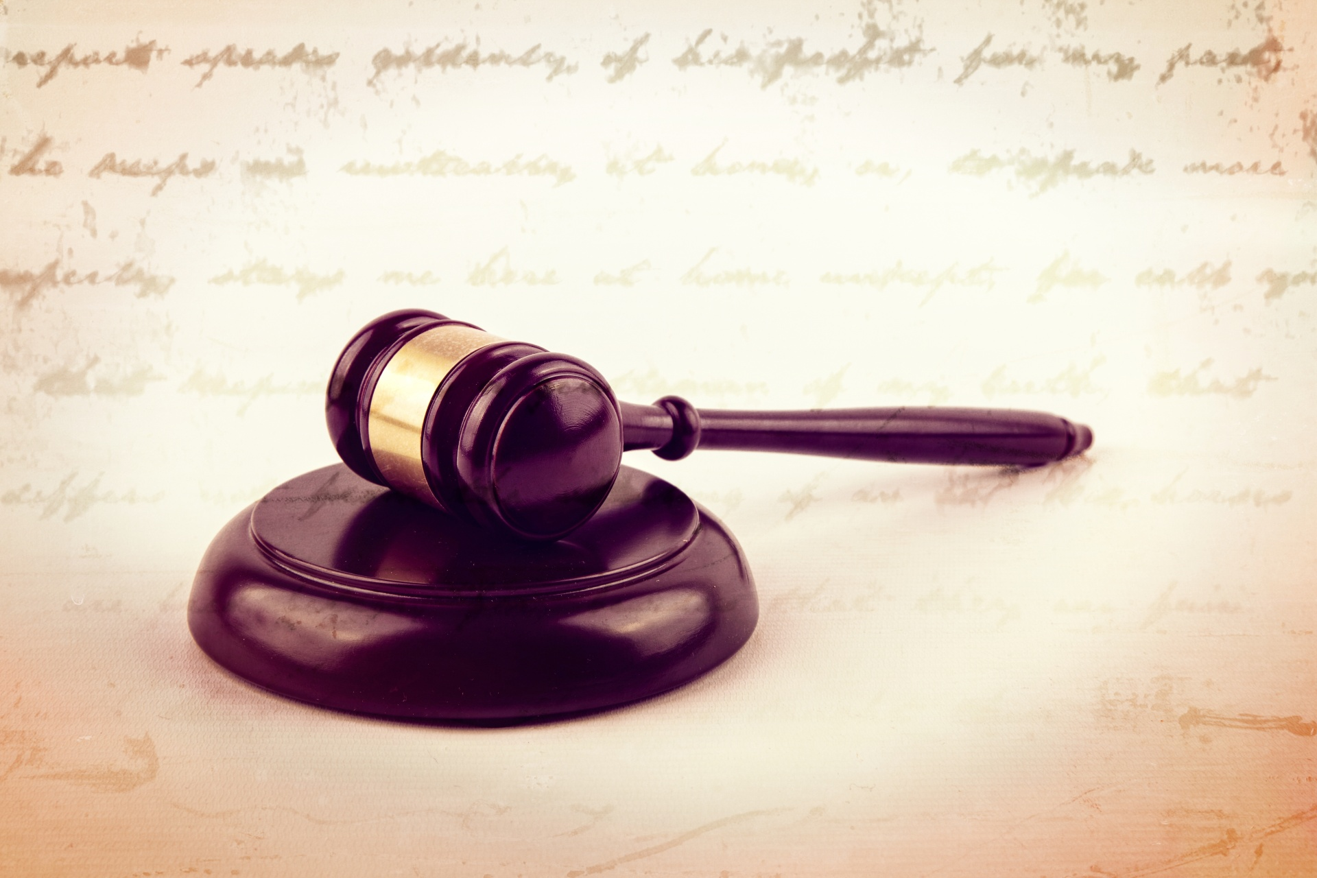 A gavel sits in front of a worn out document.