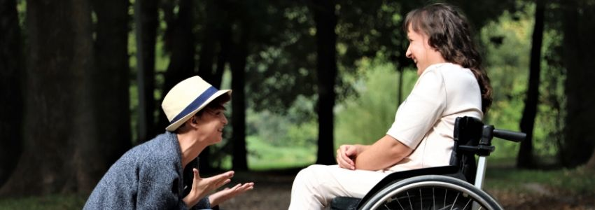 A person conversing with someone in a wheelchair.