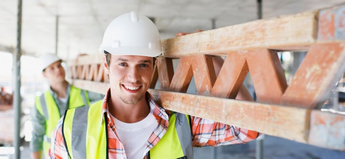 A construction worker carrying building material.