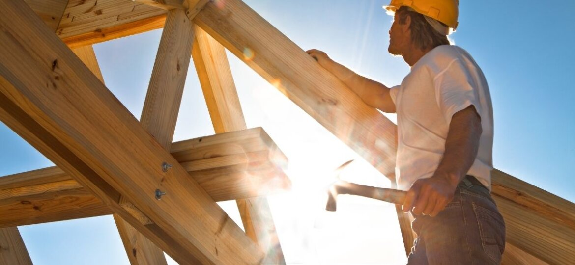 A worker standing on timber framing considering workers compensation claims.