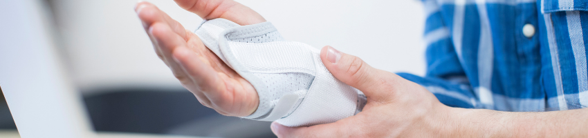 A man holding his injured and bandaged hand.