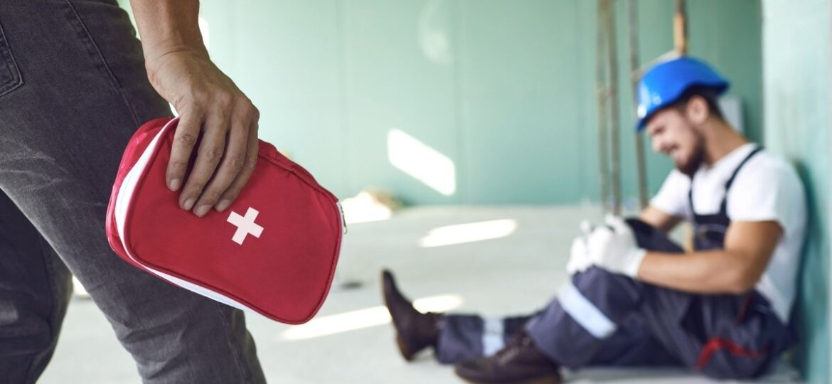 A worker applies first aid to a fellow injured worker.