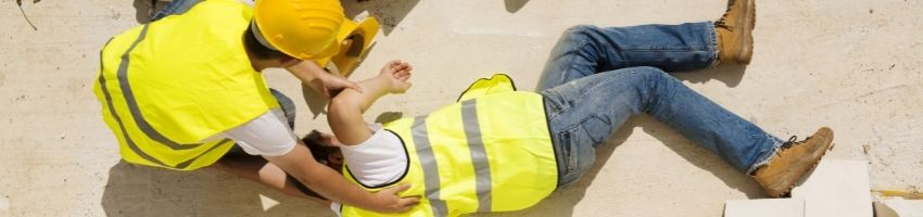 A worker in a yellow safety vest has fallen down.